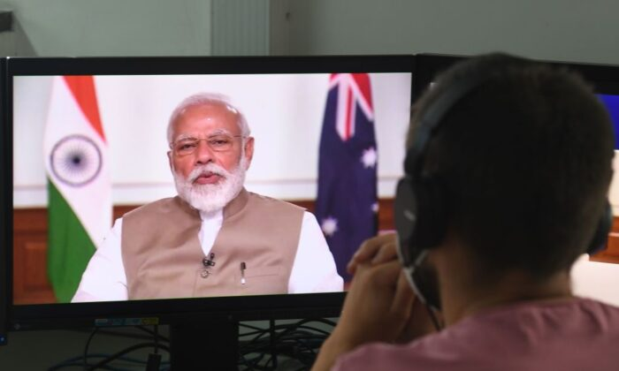 A man wearing a face-mask watches on a monitor Indian Prime Minister Narendra Modi speak during a bilateral virtual summit with Australian Prime Minister Scott Morrison, at an office in New Delhi on June 4, 2020. (Prakash Singh/AFP via Getty Images)