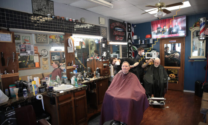 Barbers Steve Grimaldi (L) and Chris Pouch cut hair for customers at Grimaldi's Barber Shop on May 13, 2020 in Chesterton, Indiana. (Scott Olson/Getty Images)