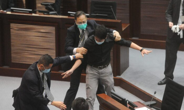 Hui Chi-fung, a lawmaker from the local Democratic Party, is restrained by security guards at Hong Kong's Legislative Council (LegCo) just before a vote on the controversial national anthem bill on June 4, 2020. (Song Bilung/The Epoch Times)