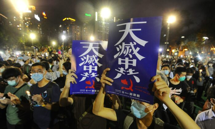 """People hold up placards with the words """"The Heavens Will Destroy the Chinese Communist Party"""" at a vigil at Victoria Park, Hong Kong, on June 4, 2020. (Song Bilung/The Epoch Times)"""