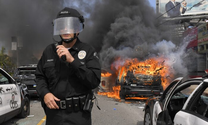 Los Angeles Police Department commander Cory Palka stands among several destroyed police cars as one explodes while on fire during a protest over the death of George Floyd in Los Angeles, Calif. on May 30, 2020. (Mark J. Terrill/AP Photo)