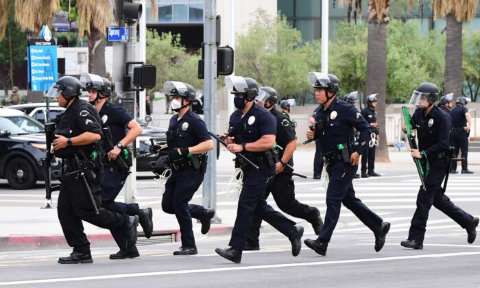 Officers from the Los Angeles Police Department run to formation during a march over the death of George Floyd, an unarmed black man, who died after a police officer kneeled on his neck for several minutes, in front of the Los Angeles City Hall in Los Angeles, Calif. on June 1, 2020. (Frederic J. Brown/AFP via Getty Images)