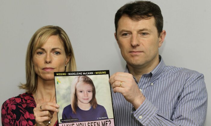 In this May 2, 2012 file photo, Kate and Gerry McCann pose for the media with a missing poster depicting an age progression computer generated image of their daughter Madeleine at nine years of age, to mark her birthday and the 5th anniversary of her disappearance during a family vacation in southern Portugal in May 2007, during a news conference in London. (Sang Tan/AP Photo)
