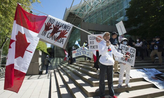 A crowd protests against Huawei on the steps of the B.C. Supreme Court during a hearing on CFO Meng Wanzhou's extradition case in Vancouver May 27, 2020. (THE CANADIAN PRESS/Jonathan Hayward)