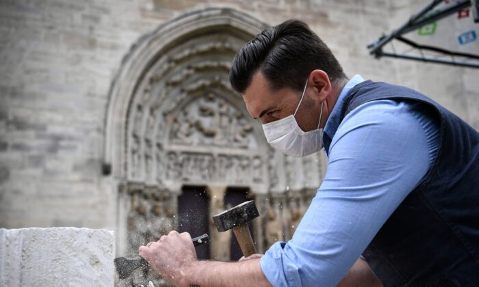 A stonemason, wearing a protective face mask, works on the forecourt of the Basilica of Saint Denis, in Saint Denis, north of Paris, France, on June 5, 2020. (Anne-Christine Poujoulat/AFP/Getty Images)