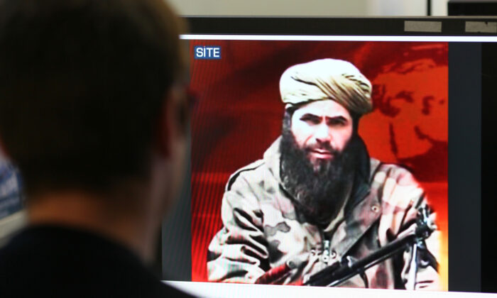 A man looks at a picture of Abdelmalek Droukdel, aka Abu Musab Abdul Wadud, head of Al-Qaeda in the Islamic Maghreb (AQIM) seen on U.S. monitoring group SITE Intelligence, in Paris  on Nov. 19, 2010. (Thomas Coex/AFP/GettyImages)