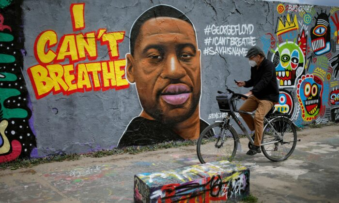 A man cycles past a mural depicting George Floyd in Berlin, Germany, on May 30, 2020. (David Gannon/AFP/Getty Images)