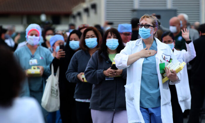 Nurses are applauded by police and firefighters as they leave Kaiser Hospital at the end of their shift in South San Francisco, California on May 14, 2020. (Justin Sullivan/Getty Images)