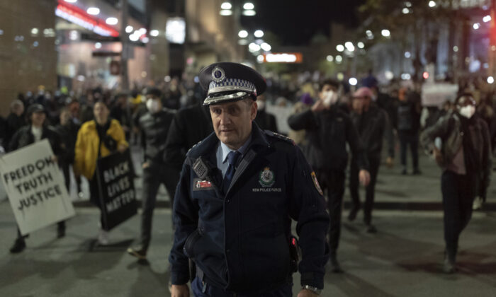 A Police officer appears walks ahead of protestors. Rally against aboriginal deaths in custody in Australia as well as in solidarity with George Floyd killing, Martin Place, Sydney, NSW, Australia, June 02, 2020. (Brook Mitchell/Getty Images)