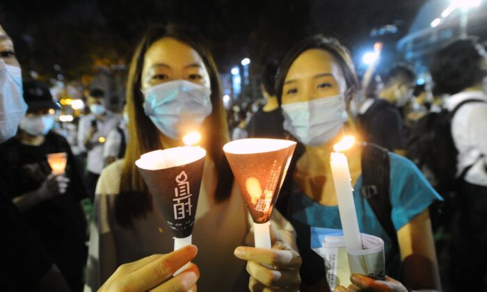 Two people hold up candles during a vigil at Victoria Park, Hong Kong, on June 4, 2020. (Song Bilung/The Epoch Times)