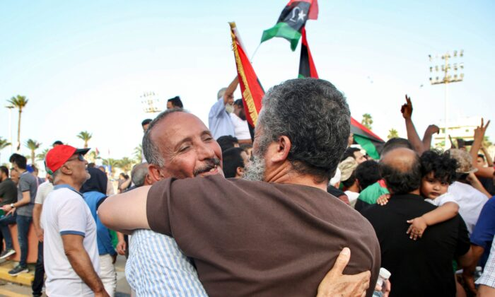 Men embrace as people celebrate in the Martyrs' Square of the Libyan capital Tripoli on June 4, 2020. (Mahmud Turkia/AFP via Getty Images)