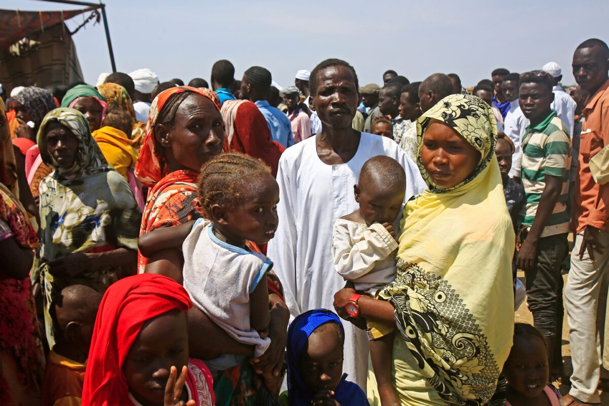 Displaced Sudanese queue to receive humanitarian aid