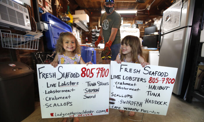 Cora Pray, left, and her sister, Pearl Pray, hold homemade signs advertising their father Eric's new business of selling his lobsters from his home garage in Portland, Maine. (AP Photo/Robert F. Bukaty)