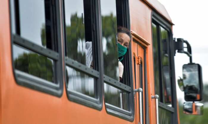 A woman wearing a face mask amid concern over the spread of the COVID-19 coronavirus, peers out the window of a bus in Havana on June 2, 2020. (Yamil Lage/AFP via Getty Images)