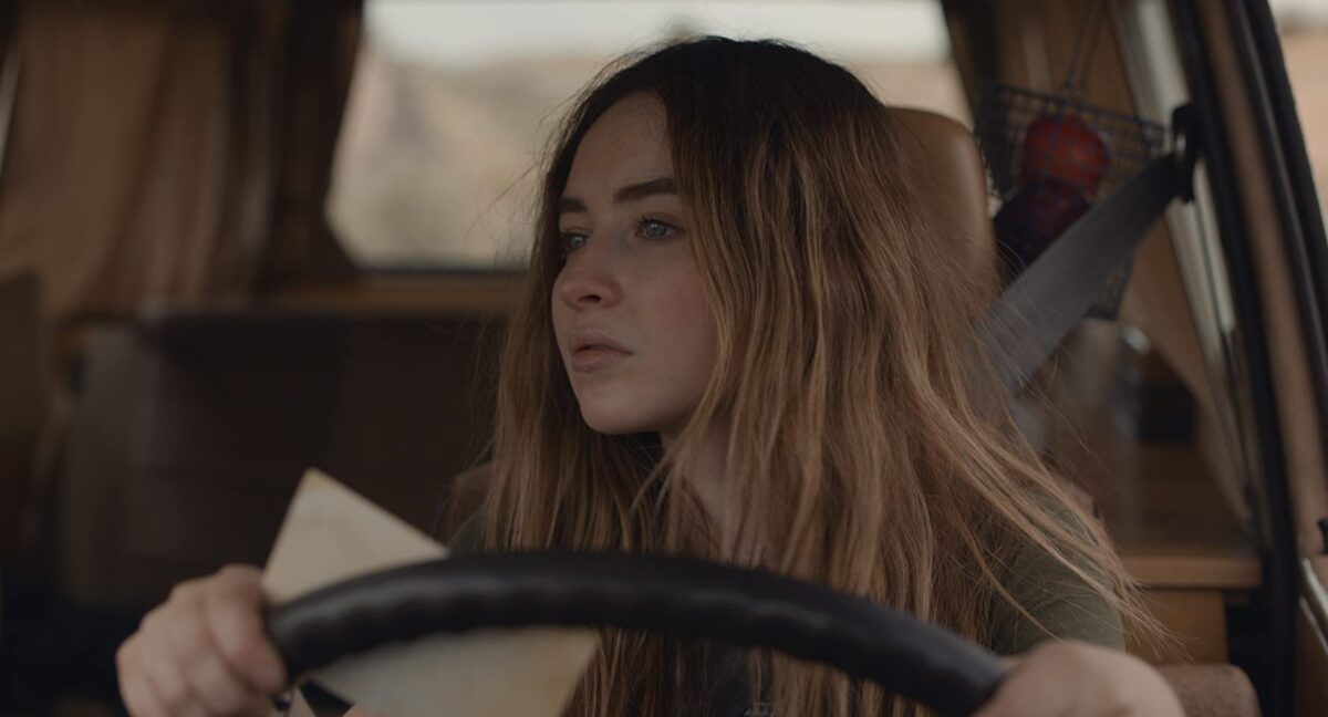 "girl behind steering wheel in ""The Short History of the Long Road"""