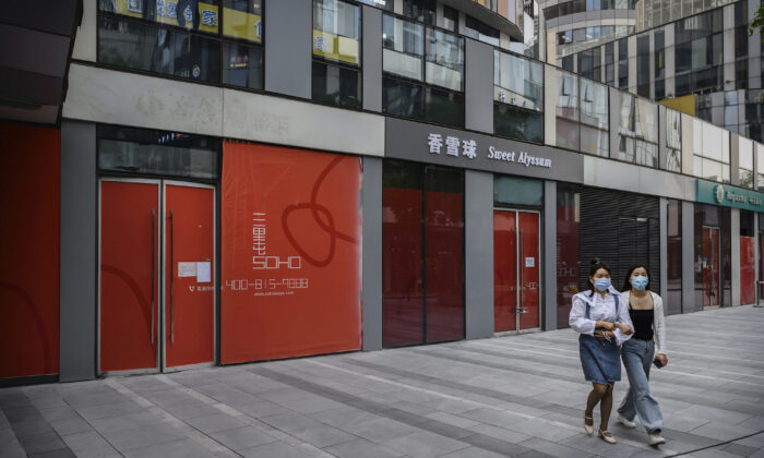 Chinese women wear   protective masks as they walk by shops that have gone out of business, in a shopping district in Beijing on April 28, 2020. (Kevin Frayer/Getty Images)