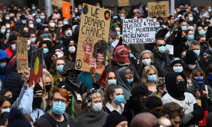 People hold up placards at a Black Lives Matter protest in Melbourne, Australia on June 6, 2020. (William West/AFP via Getty Images)