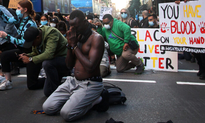A protester kneels during a 'Black Lives Matter' protest march in Sydney, Australia, June 06, 2020. (Lisa Maree Williams/Getty Images)