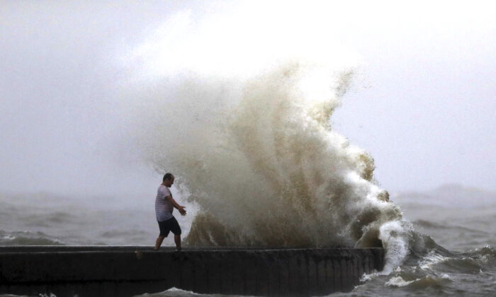 A wave crashes as a man stands on a jetty near Orleans Harbor in Lake Pontchartrain in New Orleans, as Tropical Storm Cristobal approaches the Louisiana Coast,  on June 7, 2020. (Gerald Herbert/AP Photo)