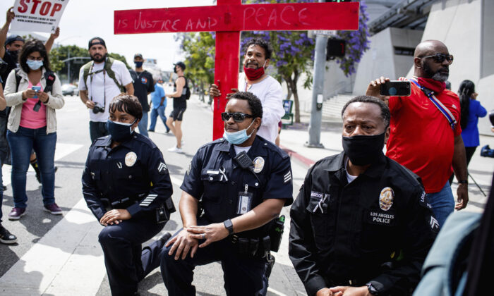 Los Angeles police officers take a knee with clergy and marchers at LAPD Headquarters during a demonstration demanding justice for George Floyd in Los Angeles on June 2, 2020. (Sarah Reingewirtz/The Orange County Register via AP, File)