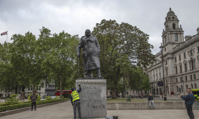 "A worker cleans the defaced statue of Winston Churchill, which was spray painted with the words ""was a racist,"" in London, UK, on June 8, 2020. (Dan Kitwood/Getty Images)"