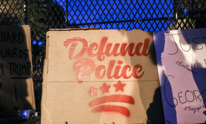 """A """"Defund the Police"""" sign during a protest near the White House following the May 25 death of George Floyd in police custody, in Washington on June 6, 2020. (Charlotte Cuthbertson/The Epoch Times)"""