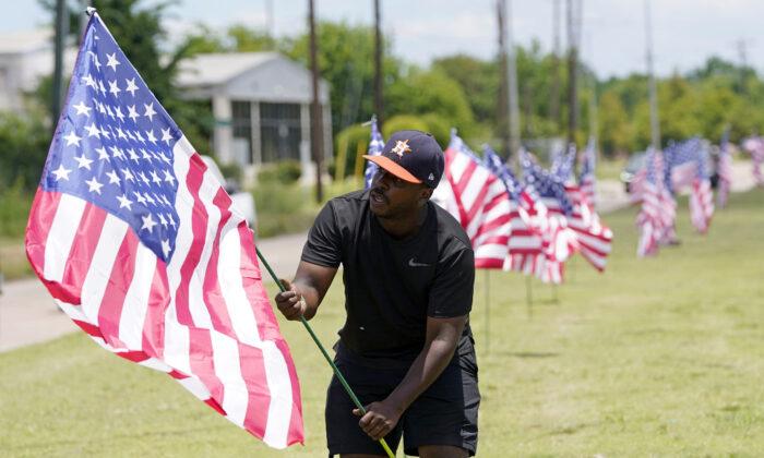 Bryan Smart plants American flags along Hillcroft Ave. as he walks toward The Fountain of Praise church in Houston, on June 7, 2020. (David J. Phillip/AP Photo)