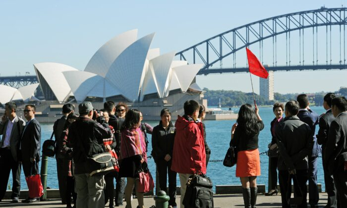 A group of Asian tourists arrive to have their photograph taken in front of the Sydney Opera House and Harbour Bridge, in this photo taken on May 8, 2012. (Greg Wood/AFP/GettyImages)
