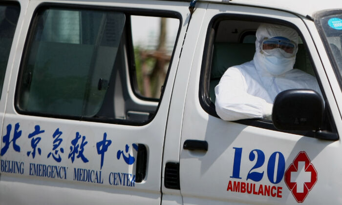 A hospital worker sits in an ambulance in Beijing's Ditan hospital in Beijing on May 17, 2009. (Feng Li/Getty Images)
