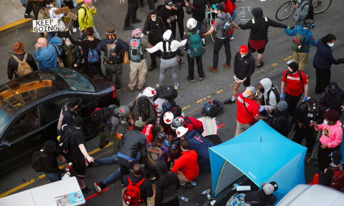Medics tend to a man who was reportedly shot in the arm by a driver at a protest in Seattle, Wash., on June 7, 2020. (Lindsey Wasson/Reuters)