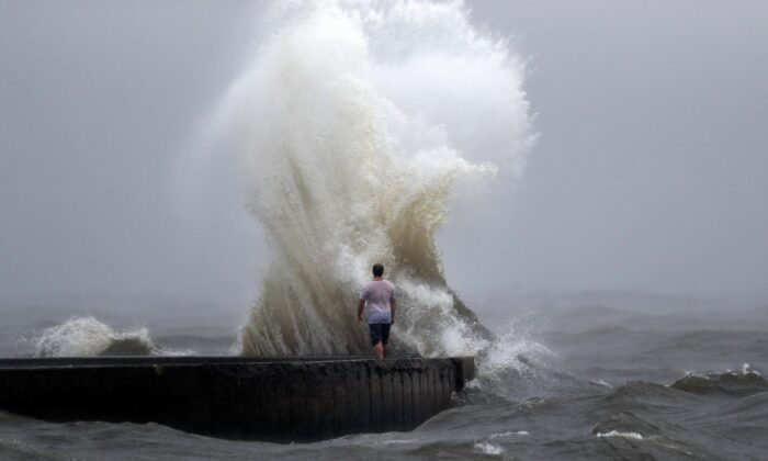 As Tropical Storm Cristobal approaches the Louisiana coast, a wave crashes as a man stands on a jetty near Orleans Harbor in Lake Pontchartrain in New Orleans, on June 7, 2020. (Gerald Herbert/AP Photo)