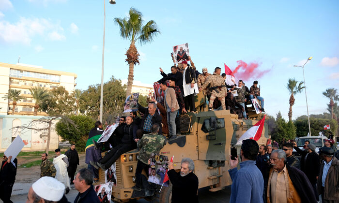 Supporters of Libyan National Army (LNA) commanded by Khalifa Haftar, celebrate on top of a Turkish military armored vehicle, which LNA said they confiscated during Tripoli clashes, in Benghazi, Libya Jan. 28, 2020. (Reuters/Staff/File Photo)