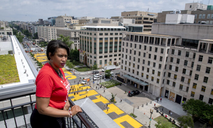 "Washington Mayor Muriel Bowser stands on the rooftop of the Hay Adams Hotel near the White House and looks out at the words ""Black Lives Matter"" that have been painted in bright yellow letters on the street by city workers and activists in Washington on June 5, 2020. (Executive Office of the Mayor/Khalid Naji-Allah via AP)"