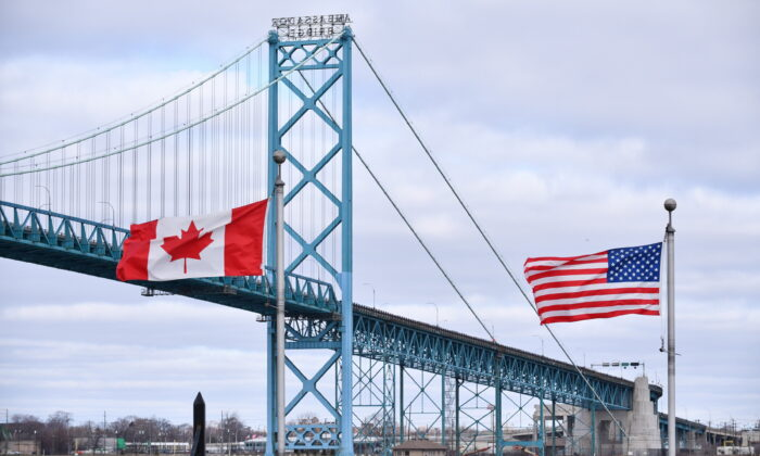 "Canadian and American flags fly near the Ambassador Bridge at the Canada-USA border crossing in Windsor, Ont. on March 21, 2020. Canada and the U.S. have mutually agreed on March 18, 2020 to temporarily restrict "" non essential traffic"" accross Canada-U.S. border due to the pandemic. (Rob Gurdebeke/THE CANADIAN PRESS)"
