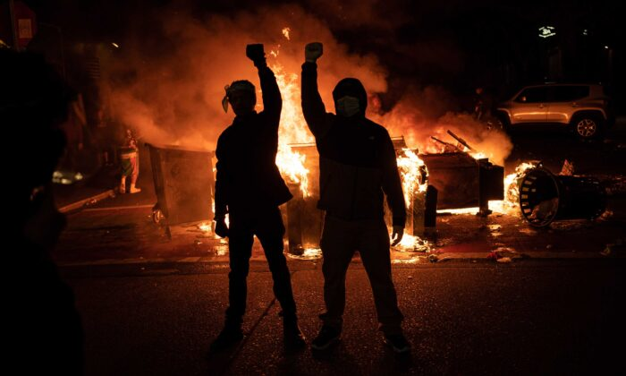 Demonstrators raise their fists as a fire burns in the street after clashes with law enforcement near the Seattle Police Departments East Precinct, in Seattle, Washington, on June 8, 2020. (David Ryder/Getty Images)