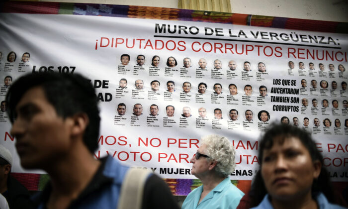 A banner depicting portraits of national deputies accused of corruption is displayed during a protest demanding the resignation of Guatemalan President Jimmy Morales, in Guatemala City on Nov. 16, 2017. (Johan Ordonez/AFP/Getty Images)