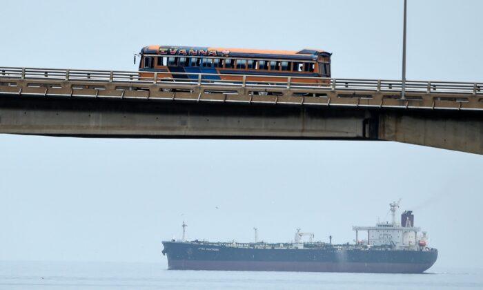 A bus drives over the General Rafael Urdaneta bridge as an oil tanker sails the Maracaibo lake in Maracaibo, Venezuela, on March 15, 2019. (Juan Barreto/AFP via Getty Images)