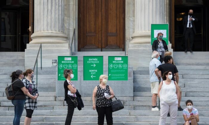 People wear face masks as they wait to enter the Museum of Fine Arts in Montreal, on June 6, 2020, as the COVID-19 pandemic continues in Canada and around the world. (The Canadian Press/Graham Hughes)