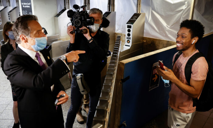 New York Governor Andrew Cuomo greets a subway rider after riding a #7 subway train in Manhattan on the first day of New York City's phase one reopening during the outbreak of the coronavirus disease (COVID-19) in New York City, New York, U.S., June 8, 2020. Mike Segar/Reuters)