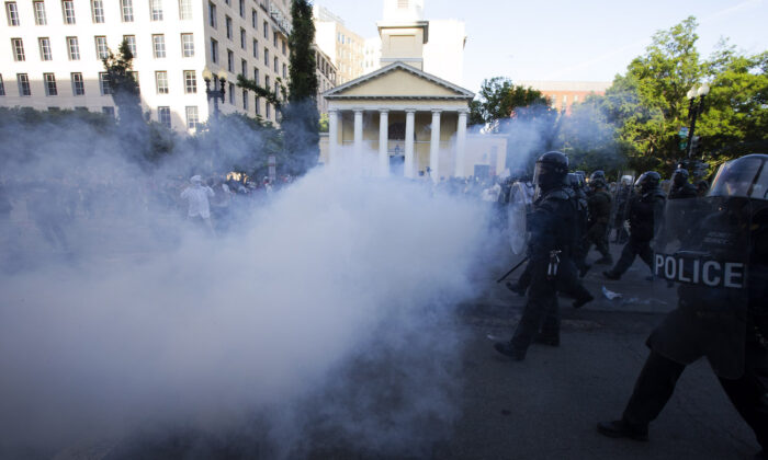 Police officers wearing riot gear push back demonstrators by deploying crowd control devices next to St. John's Church outside of the White House, in Washington, June 1, 2020. (Jose Luis Magana/AFP via Getty Images)