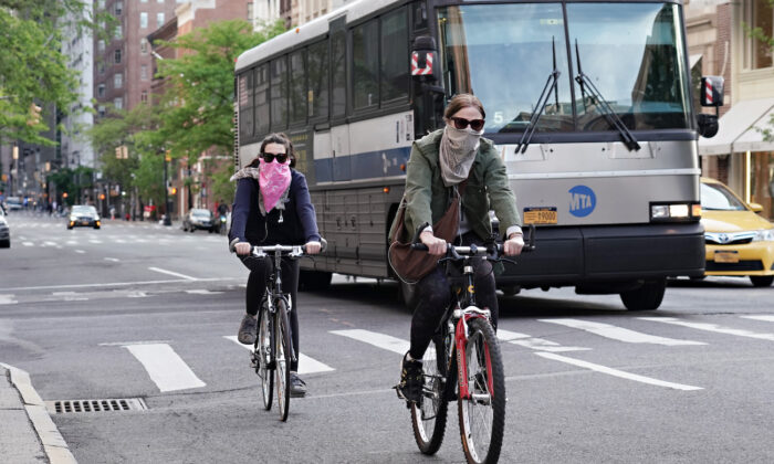 People ride bikes while wearing face coverings during the CCP virus pandemic in New York City, New York, on May 20, 2020. (Cindy Ord/Getty Images)