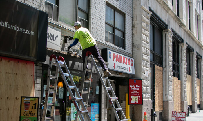 A construction worker fixes up a store sign in in Manhattan, New York on June 9, 2020. (Chung I Ho/The Epoch Times)