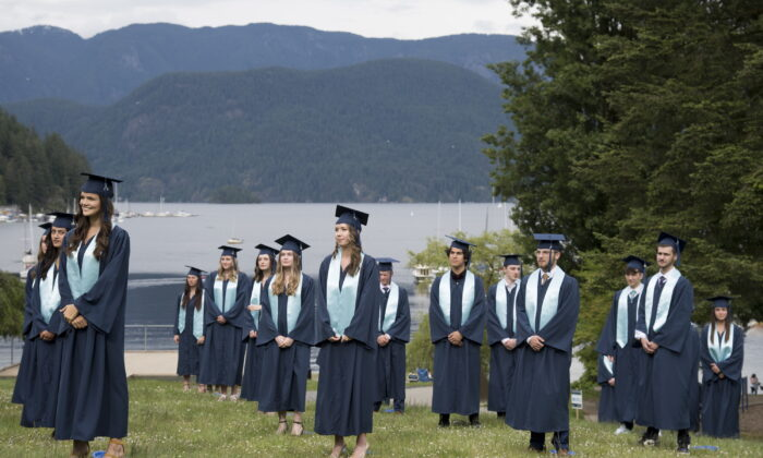 Graduating students from Seycove Secondary in Deep Cove, North Vancouver, B.C. stand physically distanced for their graduation photo on June 3, 2020.  (Jonathan Hayward/THE CANADIAN PRESS)