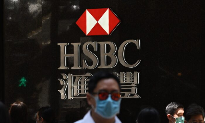 Pedestrians wear masks as they walk past an HSBC branch in Hong Kong on April 28, 2020. (Anthony Wallace/AFP via Getty Images)