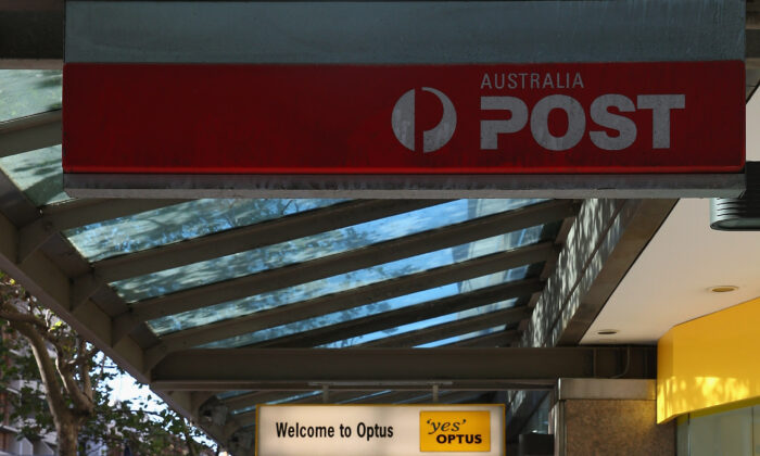 People walk down Oxford street underneath a Darlinghurst post office sign on May 7, 2014 in Sydney, Australia.(Don Arnold/Getty Images)