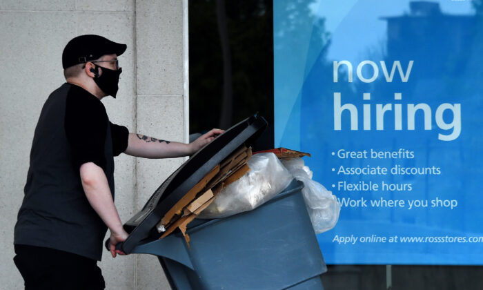 "A man wearing a face mask walks past a sign ""Now Hiring"" in front of a store amid the pandemic in Arlington, Va., on May 14, 2020.  (OLIVIER DOULIERY/AFP via Getty Images)"