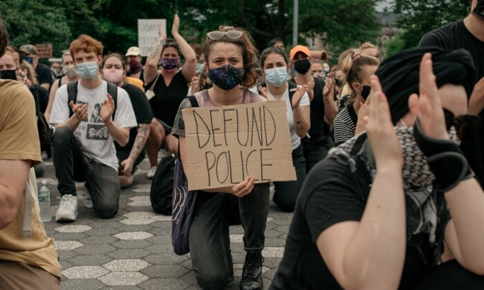 Demonstrators denouncing systemic racism in law enforcement and calling for the defunding of police departments kneel in Maria Hernandez Park in the borough of Brooklyn in New York City on June 5, 2020. (Scott Heins/Getty Images)
