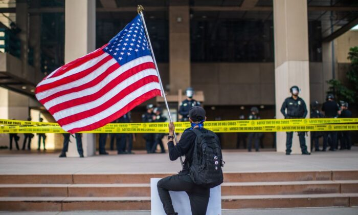 A demonstrator holding a flag kneels in front of the police at the Anaheim City Hall during a peaceful protest over the death of George Floyd in Anaheim, Calif., on June 1, 2020. (Apu Gomes/AFP via Getty Images)