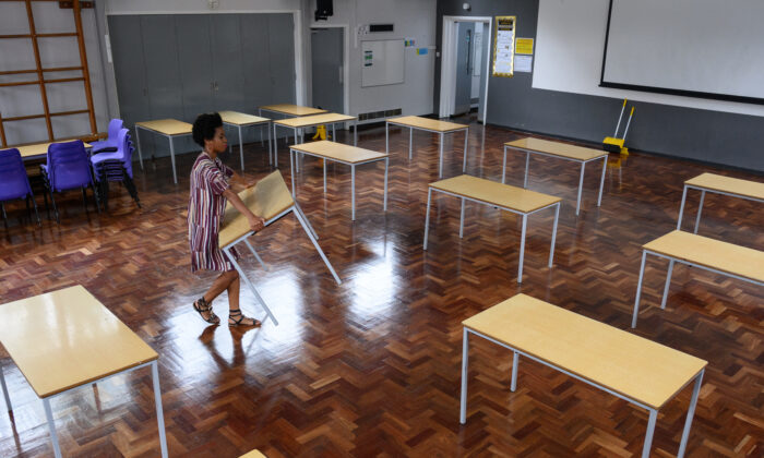 Teacher Muriel Thompson carries a desk into the temporary classroom within the school hall, ahead of the return of more students from Reception and Year Six of Muswell Hill Primary School on June 03, 2020 in London, England. (Leon Neal/Getty Images)