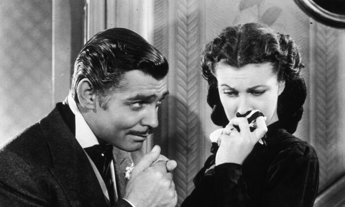 Actor Clark Gable in his role as Rhett Butler kissing the hand of a tearful Scarlett O'Hara, played by Vivien Leigh, in 'Gone With the Wind.' (Hulton Archive/Getty Images)